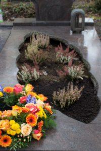 Grabgestaltung im Winter mit Blumenkranz und Winterheide